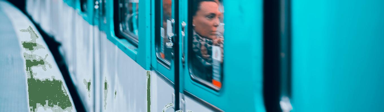 Eine Frau sitz im Zug hinter Fenster