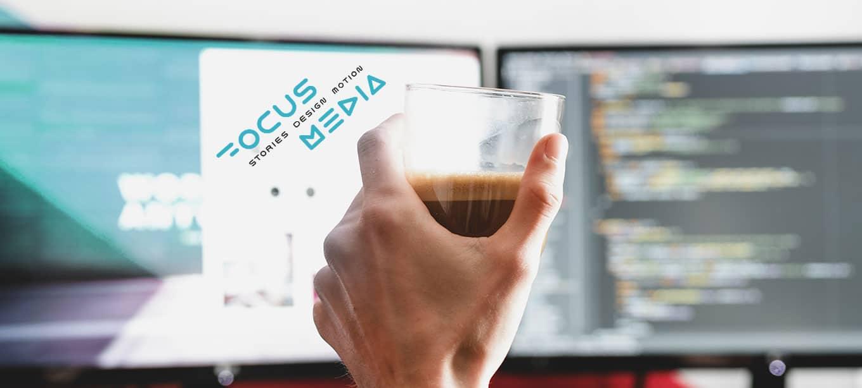 Hand mit Kaffeetasse vor FocusMedia Bildschirm