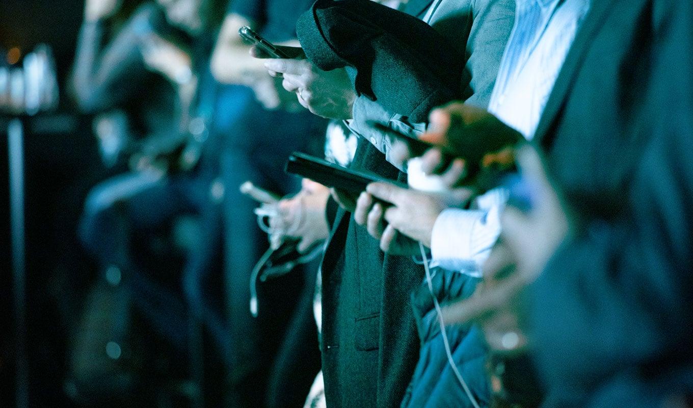 Personengruppe, alle sind mit ihrem Mobile Phone beschäftigt.