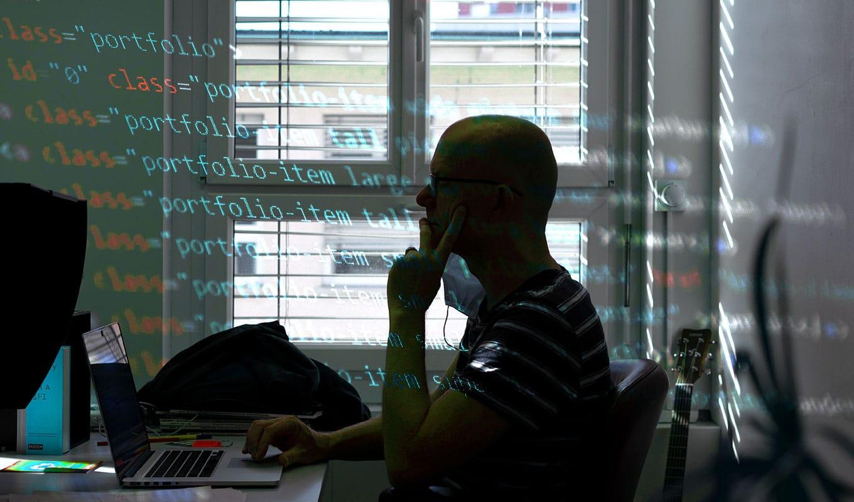 Person programmiert Codezeilen am Bildschirm