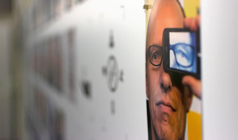 Bildwand mit Portrait, ein Mann schaut durch Mobilekamera