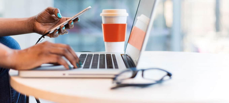 Frauenhände am Laptop und Mobile